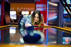 Lets Play. Young brunette long haired girl playing a very competitive game of air hockey in an arcade mall for young people Royalty Free Stock Photos