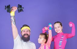 Lets practice. Sports coach and little girls building strength with dumbbells. Father and daughters exercising in gym stock image