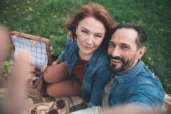 Cheerful married couple making selfie on meadow stock images