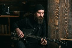 Lets rock. Rock guitarist playing music. Rock style man. Rock and roll music performer. Electric guitar player. Hipster. Musician. Bearded man play the guitar royalty free stock photos