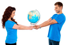 Lets save our world together. Joyous couple holding globe together and looking at each other Royalty Free Stock Photography