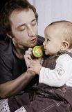 Lets talk. Young father and baby daughter playing with a toy telephone royalty free stock photo