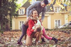 Lets tickling mother. Parents have playing with children at back. Yard.Leisure activity Royalty Free Stock Photo