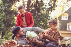 Lets tickling together a father. Happy family playing outside. Lets tickling together a father. Happy family playing oute on fallen leaves Stock Photography