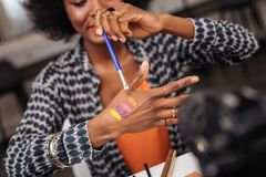 Lets try. Beautiful dark-skinned african american woman wearing a gold bracelet putting new swatches on her hand royalty free stock photos