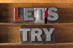 Lets try tray. Lets try phrase made from metallic letterpress type on wooden tray stock image