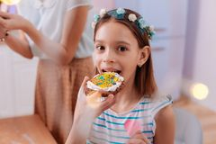 Portrait of cute girl that looking straight at camera. Lets try. Pleased brunette little female expressing positivity while eating biscuit stock photo