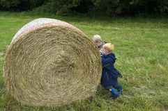 Lets work. Two boys pushing a hay bale Stock Photo