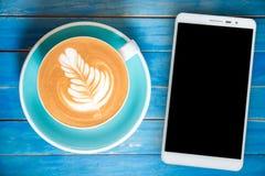 Lette взгляд сверху горячее в чашке и smartphone с пустым экраном на bl Стоковые Фото