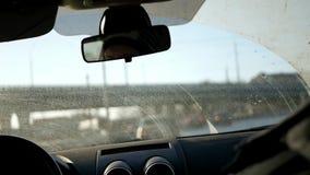 Lettend op het vuile venster van een auto die zich langs de weg onder de brug beweegt, vallen de zon` s stralen op het glas langz stock video