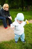 Lettende op baby in park Stock Fotografie