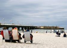 Lettende op mensen op strand. Stock Foto