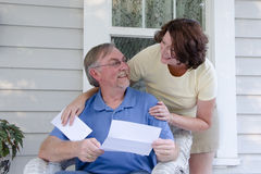 The Letter. A middle-aged couple on an old-fashioned porch look at each other while reading a letter or announcement Royalty Free Stock Photos