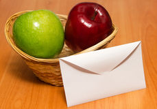 Letter against apples in a basket. One Letter against two apples in a basket on the table Stock Photos