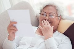 Letter. Aged woman laughing while reading a letter royalty free stock photo