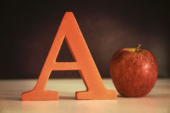 Letter A with an apple on table Royalty Free Stock Image