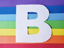 Letter B in white with background in rainbow colors. Backdrop for ads related to colors and lgbt community, graphic sign of a writing system with multicolor stock image