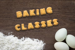 Letter biscuits word BAKING CLASSES  on kitchen table background Royalty Free Stock Image