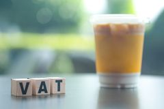 Letter block in word VAT with cup of iced coffee background stock image