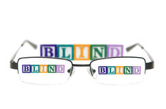 Letter blocks spelling blind through a pair of glasses. Letter blocks spelling blind through glasses. Isolated on white Stock Images