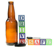 Letter blocks spelling drive safe with a beer bottle. Isolated on a white background Royalty Free Stock Image