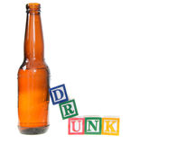 Letter blocks spelling drunk with a beer bottle. Isolated on a white background Royalty Free Stock Photography