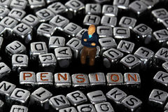 Letter blocks spelling pension with model pensioner. Letter blocks spelling pension with scale model male pensioner Stock Photography