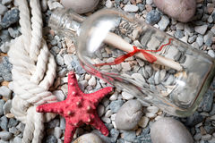 Letter in bottle on stones with starfish and marine knot. Letter in bottle on stones with red starfish and marine knot Stock Images
