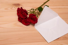 Letter and a bouquet of red roses on wooden background Royalty Free Stock Photo