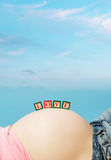 Letter boxes on pregnant woman belly Stock Photo