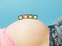 Letter boxes on pregnant woman's belly Royalty Free Stock Image