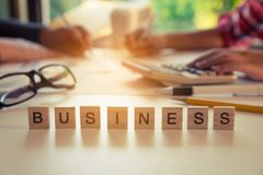 The letter `BUSINESS` is on the table with business people working behind the scenes - Business team collaboration ideas. Stock Photography