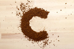Letter C, alphabet from coffee beans. Isolated on wood royalty free stock image