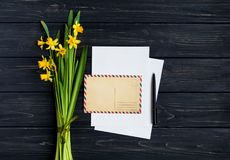 Letter, envelope and daffodils on dark wooden background. Romantic holiday concept, top view, flat lay royalty free stock photo
