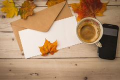 Letter with coffee cup and smartphone on wooden background Stock Image