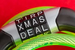 Letter combination bike lock with Xmas Deal code. To unlock the steel security cable covered in green plastic over a festive red holiday background in a stock image