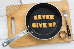Letter cookies quote NEVER GIVE UP and kitchen utensils Royalty Free Stock Photography