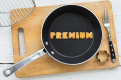 Letter cookies word PREMIUM and kitchen utensils. Top view of letter collage made of cookies. Word PREMIUM putting in black pan. Other kitchen utensils: fork Royalty Free Stock Photography