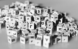 Letter Cubes. Black & white letter cubes lying on a grey surface royalty free stock photography
