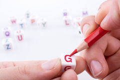Letter cubes. Hand holding pencil with Letter cubes on a white background Stock Photos