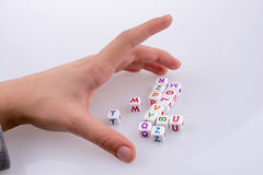 Letter cubes. Hand playing with Letter cubes on a white background Stock Photography