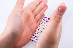Letter cubes. Hand playing with Letter cubes on a white background Stock Photo