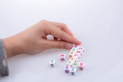Letter cubes. Hand playing with Letter cubes on a white background Royalty Free Stock Photos