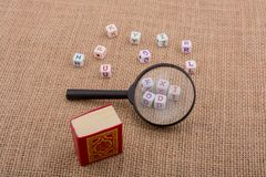Letters, magnifying glass and the Holy Quran. Letter cubes, magnifying glass and the Holy Quran Stock Photos