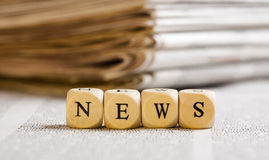Letter Dices Concept: News. Concept of dices with letters forming word: News. Generic newspaper background with some blurred text on the bottom and paper stack Royalty Free Stock Images