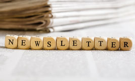 Letter Dices Concept: Newsletter. Concept of dices with letters forming word: Newsletter. Generic newspaper background with some blurred text on the bottom and Stock Images