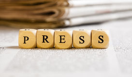 Letter Dices Concept: Press. Concept of dices with letters forming words: Press. Generic newspaper background with some blurred text on the bottom and paper Stock Photo