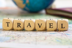 Letter Dices Concept: Travel. Concept of dices with letters forming words: Travel. Blurred map, globe and passport as background Stock Images