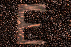 Letter E inscription with coffee bean on the wooden table. Top view. Copy space. Still life. Mock-up. Flat lay Royalty Free Stock Photography
