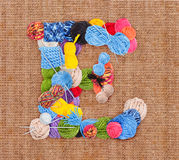 Letter E. Made of knitting yarn on burlap background Stock Photography